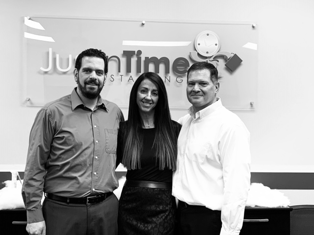 Black and white photo of three employees (two men, one women) standing next to each other in front of a wall with the Just in Time Staffing logo behind them.