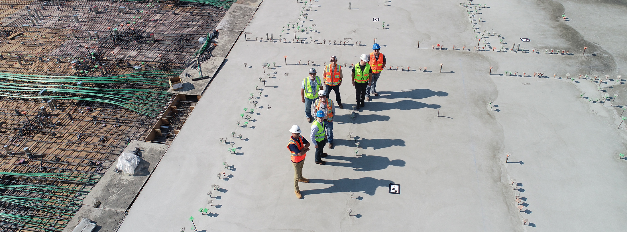 View from above of 7 men in safety vests and hardhats on a construction site.