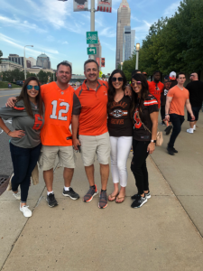 5 JITS employees in orange and black sports jerseys standing together on a sidewalk