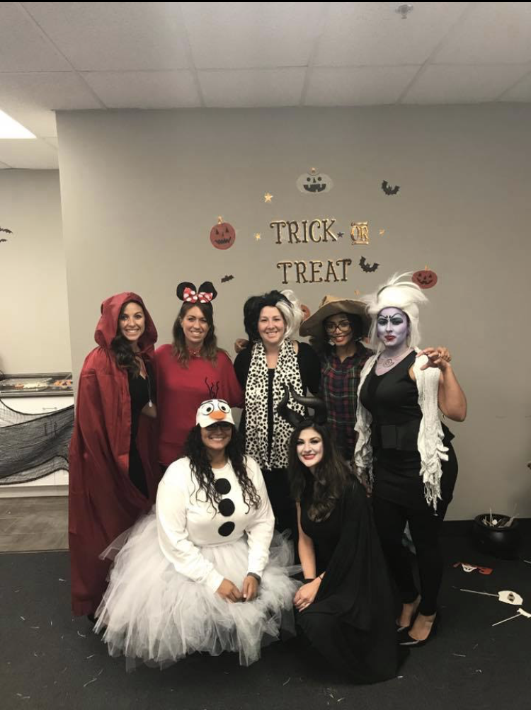 7 women in halloween costumes standing in front of office wall with the words Trick or Treat