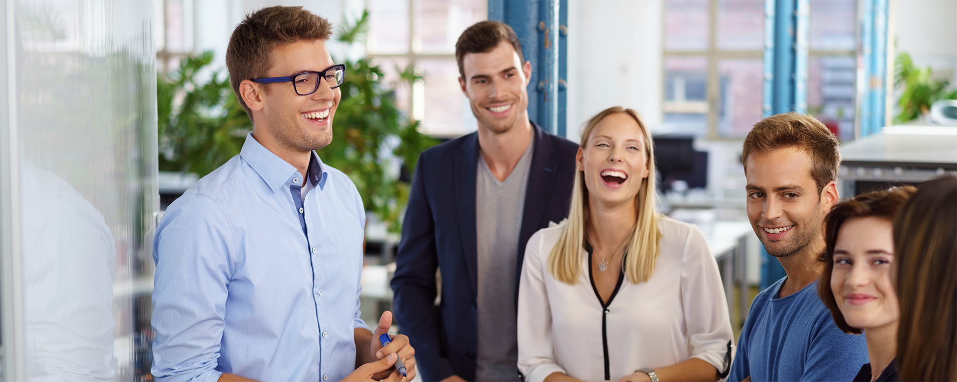 Five people in office attire standing together and laughing