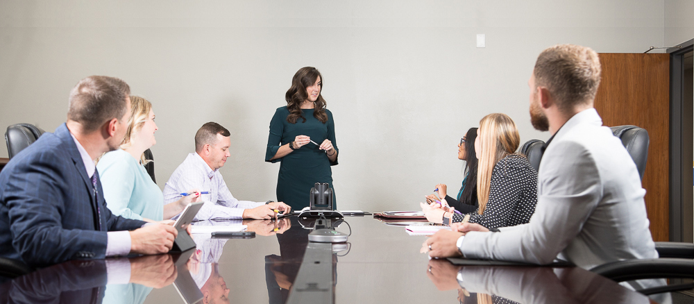 Woman in green business dress standing and talking to 6 people in business attire who are seated at a conference table.