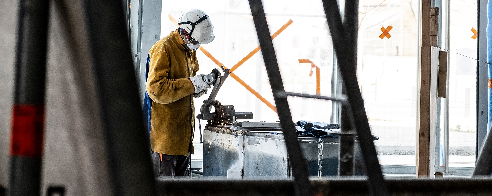 Industrial job worker wearing COVID mask and white hard hat in industrial setting while cutting metal
